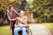 senior man in wheelchair with happy caregiver daughter
