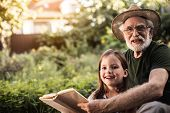 Senior Man Sitting With Grandchild Outside In Backyard poster