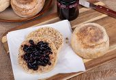 Overhead View Of An English Muffin Cut In Half And Spread With Blueberry Preserves On A Napkin Along poster