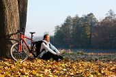 stock photo of peppy  - Peppy woman cyclist with bike sits among fallen leaves autumn morning in nature illuminated by the rays of the rising sun - JPG