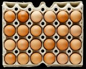two dozen brown eggs in a tray, above view, isolated on black