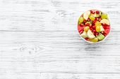 Fruit Diet Concept. Fruit Salad With Apple, Kiwi And Pomegranate In Bowl On White Wooden Background  poster