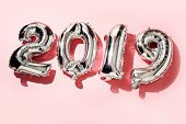 some silvery number-shaped balloons forming the number 2019, as the new year, on a pink background poster