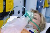 Mulher inconsciente com máscara de oxigênio, interior de ambulância