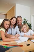 Smiling family doing homework together