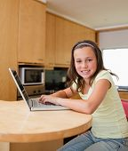 image of online education  - Girl with her laptop sitting at the kitchen table - JPG