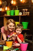 Growing Concept. Little Child And Mother Sprinkling Young Plant Growing In Pot. Pot Plant Growing. A poster