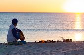 Traveler Sits Next To A Bonfire On The Seashore Meditates And Admires Sunset Over The Sea. Awesome T poster