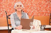 Older woman perusing a restaurant menu