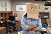 Businessman hiding face inside a cardboard box with sad depressed smile on it. Mature man wearing sa poster