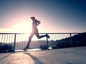 Attractive Wiry Man Jogging Against To Sun. Regular Morning Training At Sea. Young Sportsman Jogging poster