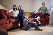 Interracial family of five sitting together on living room sofa watching television