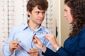 Attractive saleswoman helps young handsome guy buy eyeglasses, background in optician shop