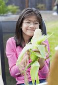 Girl Peeling Husk Off Corn Cob