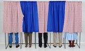 A row of five voting booths with men and women casting their ballots at a polling place. Horizontal