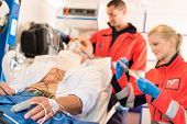 Sick patient with paramedics in ambulance treatment aid emergency work
