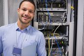 Man smiling and standing in front of data servers