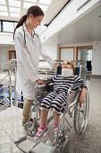 foto of neck brace  - Female doctor smiling at child in wheelchair and neck brace in hospital corridor - JPG