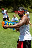 Muscular Young Man Squirts People With Water Gun