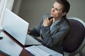 Thoughtful Business Woman Sitting At Desk In Hotel Room