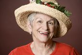 stock photo of old lady  - Senior woman in a red shirt and straw hat - JPG