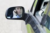 Male Driver Seen Through Side-view Mirror Of Car.