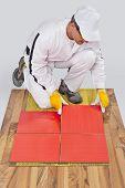 Worker Applies Ceramic Tiles On Wooden Floor With Fiber Mesh