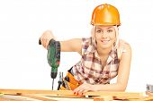 Female carpenter with helmet at work using hand drilling machine isolated on white background