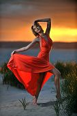 Young fashion model posing in red dress on sunset time