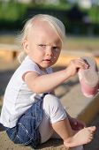 Toddler Put On Her Shoes Near Sandbox