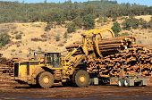 stock photo of wheel loader  - A large wheeled loader unloads a log truck at a small log sawmill in Oregon - JPG