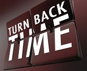 The words Turn Back Time on flipping tiles on a retro clock to illustrate going backward to the past
