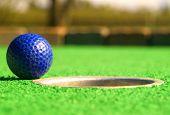 stock photo of miniature golf  - a golf ball on the edge of the hole - JPG