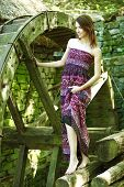 beautiful young woman and old watermill