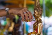pouring water over Buddha statue