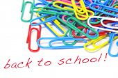 sentence back to school written in red on a white background, with many paperclips of different colors
