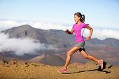 Female running athlete. Woman trail runner sprinting for success goals and healthy lifestyle in amazing nature landscape. Cross country run with fit female fitness model running at fast speed.
