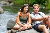 People hiking - resting hikers portrait at river. Portrait of woman and man hiker looking at camera