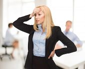 picture of insulting  - stressed woman holding her head with hand in office - JPG