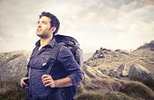 handsome man with a sack on his back walking in the mountains