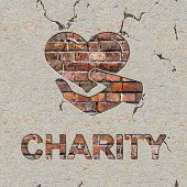 stock photo of word charity  - Charity Word and Icon of Heart in the Hand on the Brick Wall - JPG