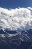 Winter Mountain With Clouds And Silhouette Of Parachutist