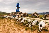 stock photo of mongolian  - Mongolian stone shrine or Ovoo with ceremonial prayer flags called khadag and horse skulls - JPG