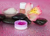 Aromatic oil, salt, candle, stones and flower
