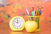 Stationery, alarm clock and apple