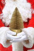 Father Christmas holding a gold Xmas tree against his traditional red suit