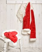 Santa's hat and gold rimmed specs on stool with coat hanging in the background