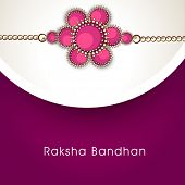 Beautiful pink rakhi with golden color thread on purple on grey background for the festival of Raksh