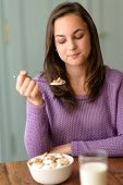 Young woman eating healthy cereal breakfast looking down