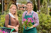 Smiling customer and worker in garden center holding potted plant